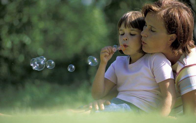 Äiti ja lapsi puhaltamassa saippuakuplia