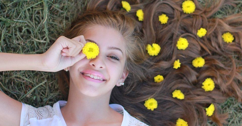 Tyttö nurmikolla ja kukkia