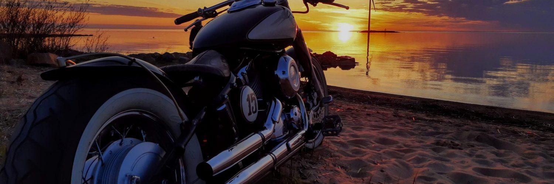 moottoripyörä merenrannalla varjakassa